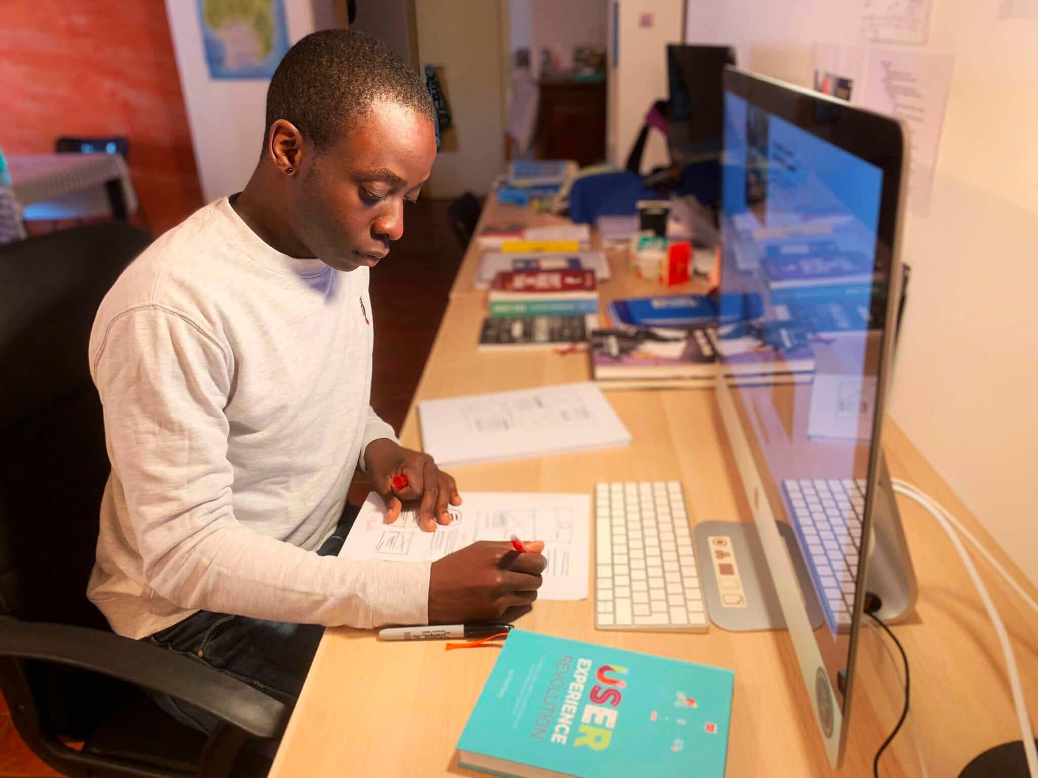 Jerome Kalumbu working at his home office in Milan